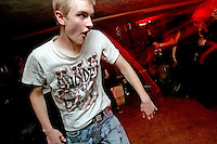 James Gregory of Grayslake, Illinois, dances during a punk concert in the basement of the White House in Woodstock, Illinois.  The White House was a small suburban residential home rented by a group of 20-somethings in Woodstock, Illinois, a distant northwestern suburb of Chicago.  For about a year, the renters of the house staged punk-rock concerts in the house's small basement, without the approval of the neighborhood, local government, or police.  .