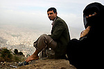 A Yemeni man and woman on holiday from the Western city of Hudaydah relax above the city of Taezz, Yemen, Nov. 30, 2009. A raging conflict with Houthi rebels in Yemen's north and clashes with separatists in the South continue to erode stability in the Arabian Peninsula's poorest state, where half of the population lives in abject poverty.