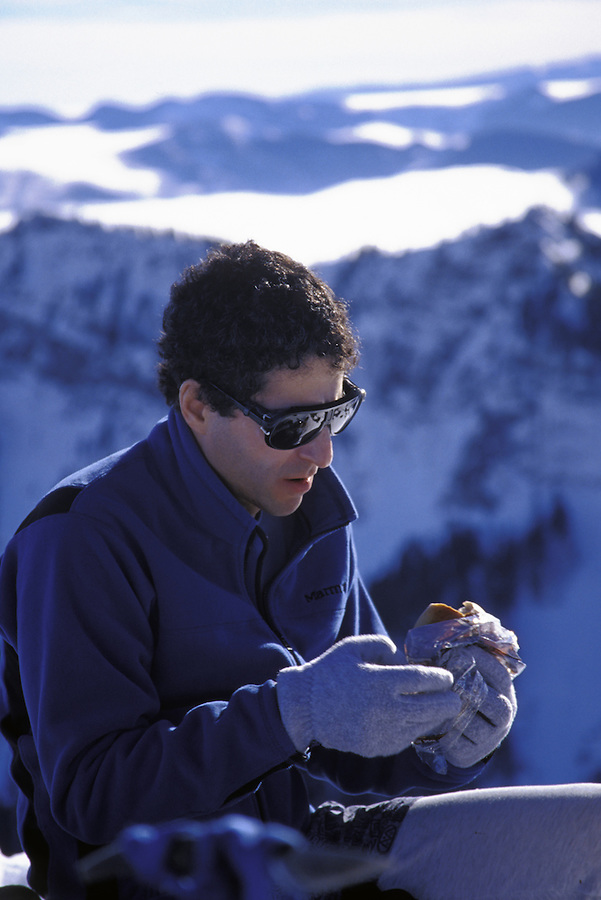 Man eating in snowy backcountry, Silver Peak, Mt Baker-Snoqualmie National Forest, Cascade Mountains, Washington