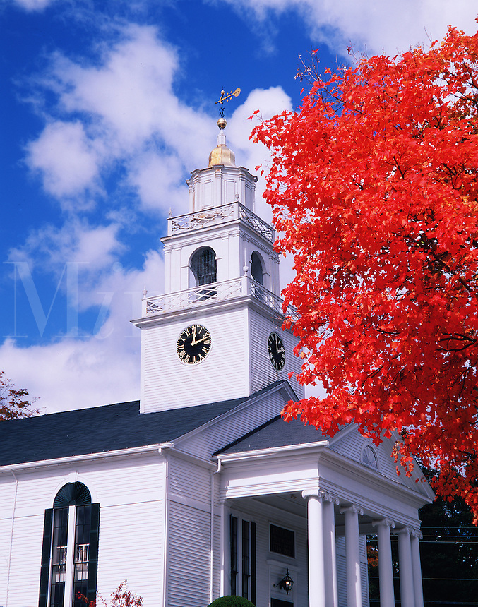 The exterior of the Bedford Presbyterian Church under a bright blue sky and fluffy white clouds. A nearby tree with fiery red fall foliage provides a striking color contrast. Bedford, New Hampshire.