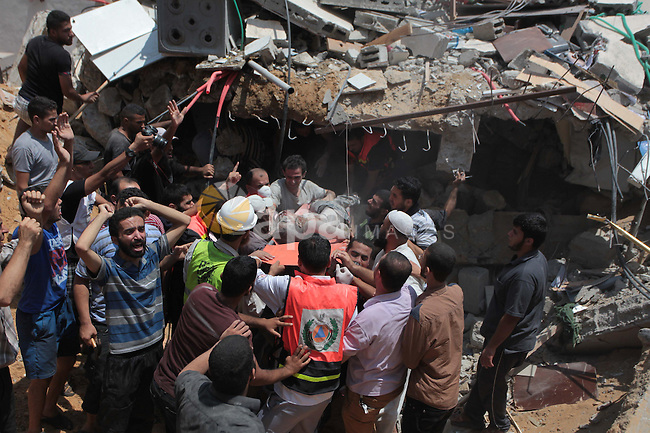 Palestinian rescue workers and civilians remove a lifeless body from the rubble of a house was destroyed by an Israeli missile strike, in Gaza City, Monday, July 21, 2014. On Sunday, the first major ground battle in two weeks of Israel-Hamas fighting exacted a steep price, killing scores of Palestinians and over a dozen Israeli soldiers and forcing thousands of terrified Palestinian civilians to flee their devastated Shijaiyah neighborhood, which Israel says is a major source for rocket fire against its civilians. Photo by Ashraf Amra