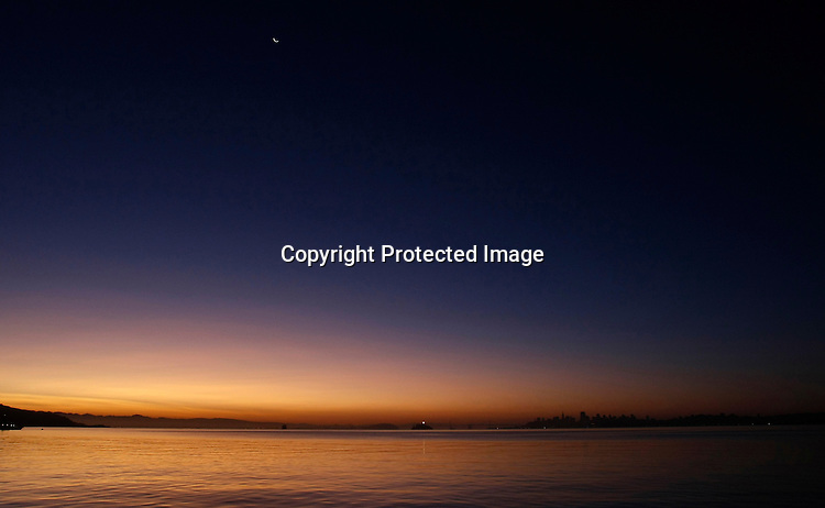 The bay appeared to be like a glass just before sunrise as scene from the shore of Bridgeway in Sausalito.