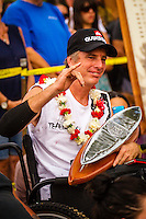 "HONOLULU, Oahu, Waimea Bay - Thursday, November 28, 2012 -- Water Cinematographer Mike Prickett (HAW), who was paralysed in a diving accident, recieved a Waterman's award during the 28th annual Quiksilver In Memory of Eddie Aikau official opening ceremony and blessing today at Waimea Bay on the North Shore of Oahu today. The ceremony  featured this year's 28 Invitees, including newly elected riders John John Florence (Hawaii), Ian Walsh (Maui), and Alex Gray (California), as well as former ""Eddie"" champions Kelly Slater (Florida), Greg Long (California), and Ross Clarke-Jones (Australia). The surfers will be joined by members of the Aikau family, including Eddie's younger brother and Invitee Clyde Aikau...When the Invitees and Alternates paddled out and grouped in the traditional surfer's circle it's about camaraderie and making a connection to the others who will ultimately share in your experience and watch out for your safety..The holding period for the Quiksilver In Memory of Eddie Aikau will commence on Saturday, December 1, and runs through  to February 28, 2013. The event requires one day of quality waves in the giant range of 20 feet or more. Waves of this size are only generated occasionally by hurricane force winds from intense storms in the Pacific NW. The elements of wind, swell height and arrival time to the island's shore must be in perfect alignment to allow a full eight hours of daytime competition..Waimea Bay was Eddie Aikau's home away from home. It was here that he saved countless lives as the Bay's first official lifeguard, and successfully rode the largest waves of his day. An early pioneer of big wave riding in Hawaii, Eddie has inspired generations of ""storm surfers"" who today roam the globe year-round in search of giant waves..The Quiksilver In Memory of Eddie Aikau has only been held a total of eight (8) times, most recently on December 8, 2009. California's Greg Long (California) took the honor that year. .Photo: joliphotos.com"