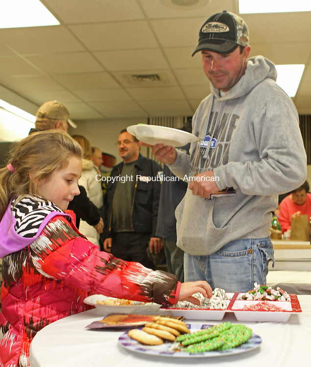 Torrington, CT-120513MK03 Mike Sirois looks on as his daughter Gabriella selects a cookie just after the lights on The North End Community Tree were lit Thursday evening at the Torrington police department. Attendees of the event rushed inside to avoid the weather and enjoy pizza, hot chocolate and other treats. Glenn Royals, vice president of the North End Community Association said that just over fifty people braved the rain and fog to listen to carols while watching the lighting of the tree.  Royals said that the group began in 1934 by businesses of the North end and over time have funded various events and purchased equipment for the town's police and fire departments.  This was the fourth year that the Frasier Fir tree, donated and planted by Mike Sirois of  North West Landscaping, was decorated with lights.  Michael Kabelka / Republican-American