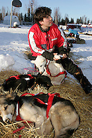 Ramy Brooks puts booties on his dogs prior to leaving the Nikolai checkpoint.  2005 Iditarod Trail Sled Dog Race.