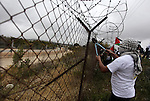 Palestinian activists cut a part of a fence near Israel's Ofer military prison and the West Bank city of Ramallah April 17, 2013. The activists cut part of the fence on Wednesday which coincides with the annual Palestinian Prisoners Day. Photo by Issam Rimawi