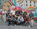"A group of photographers from ""Friends of Photography"" pose in against a mural in Chinatown, San Francisco, CA."