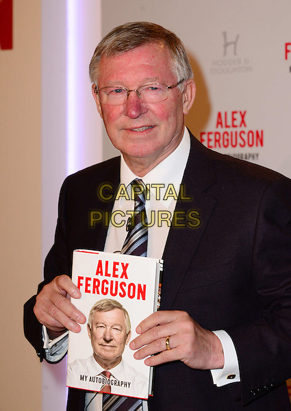 Alex Ferguson attends a photocall and press conference to promote his new autobiography - My Autobiography, Institute Of Directors, London, England.<br /> 22nd October 2013<br /> half length book black suit tie white shirt glasses <br /> CAP/BF<br /> &copy;Bob Fidgeon/Capital Pictures