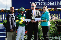 Spring Venture, with jockey P. Husband visits the winners circle and accepts winning from Tom Robbins (2nd from Right) after a winning finish at Woodbine Race Course in Ontario, Canada on September 15, 2012.