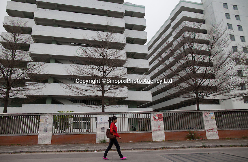 A woman walks past a Yue Yuen Industrial Holdings Limited factory dormitory building in Dongguan, Guangdong Province, China, 03 March 2015.