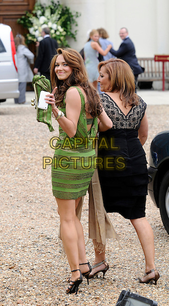 KARA TOINTON.arriving at Joe Cole's wedding.Royal Hospital, Chelsea, London, England .June 20th, 2009.full length green gold dress striped stripes looking over shoulder clutch bag.CAP/DH.©David Hitchins/Capital Pictures