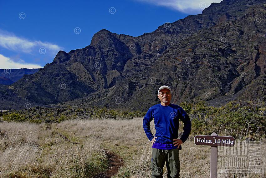 Babyboomer, local island resident, hiking at Haleakala near holua mile marker sign