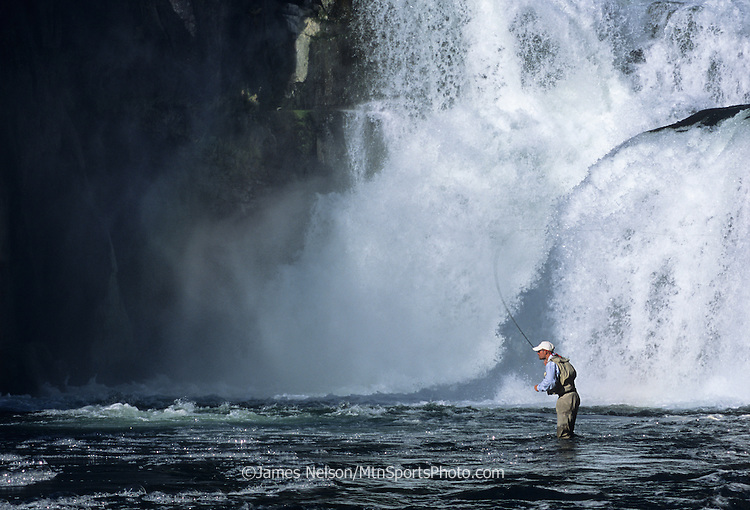 08755-C. An angler casts a fly for trout at the base of Lower Mesa Falls on the Henry's Fork of the Snake River, Idaho.