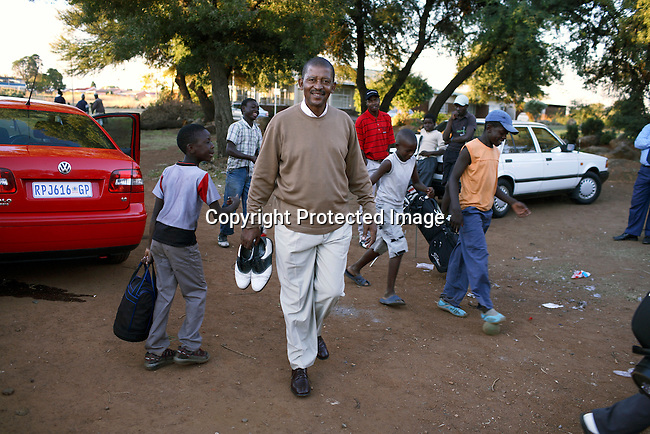 A member in the Soweto county club prepares for a round of golf. Many small boys wants to be a caddie for him.