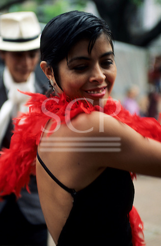 Buenos Aires, Argentina. Tango dancer with red feather boa.