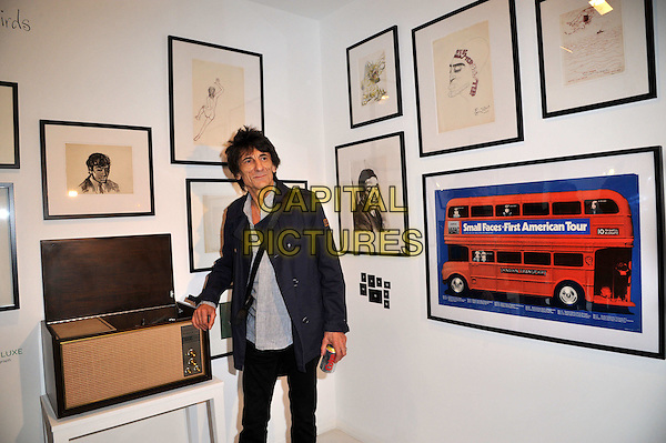 Ronnie Wood.Ronnie Wood attends a Major Retrospective of 50 Years of Rock and Roll. Rolling Stone guitarist, artist and radio DJ chats to press as he unveils a new collection of artworks alongside Rolling Stones artifacts and memorabilia. Features paintings, sketches, handwritten lyrics and guitars. Symbolic London, London, England..August 13th, 2012.half length blue jacket grey gray top diet coke can soda pop pictures frames   .CAP/BF.©Bob Fidgeon/Capital Pictures.