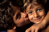 Rio de Janeiro, Brazil. Two smiling children kissing each other.