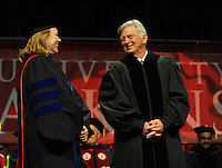 NWA Media/ANDY SHUPE - Gov. Mike Beebe, right, winks and smiles at Sharon Gaber, provost and vice chancellor for academic affairs at the University of Arkansas, before receiving an honorary degree during fall commencement exercises Saturday, Dec. 20, 2014, at Barnhill Arena on the university campus in Fayetteville.