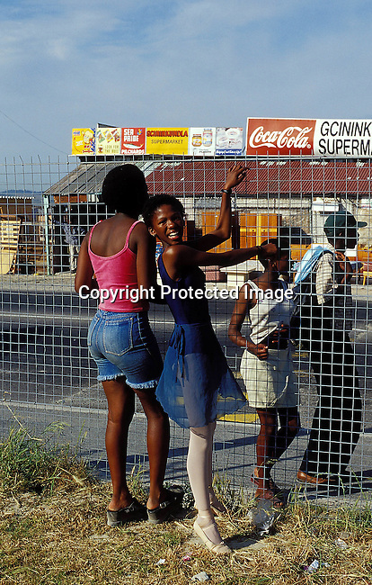 LSTEENA30005.Lifestyle. Teenager. Two teenage girls standing with their hands against a fence and another teenage girl standing at the other side. Leotard, smiling. shop. 99..©Per-Anders Pettersson/iAfrika Photos