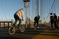 (051114-SWR002) New York, NY - 14 November 2005 -- Cyclists on BMX bikes pass tourists on a shared path across the Brooklyn Bridge .