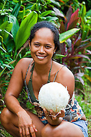 Young Tahitian woman offering coconut and a smile