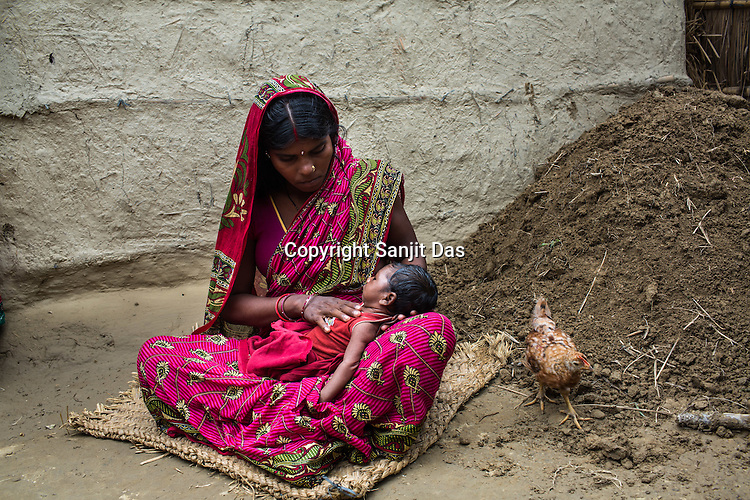 25 year old Sri Kanthi Devi holds her 3 months old son, Chandan Kumar in her house in Ramgarwa village in Raxaul district in Bihar, India.