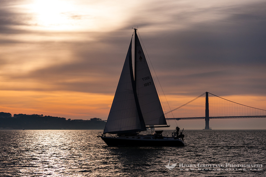 United States, California, San Francisco. Sunset view from Alcatraz, a sailboat in front of the Golden Gate bridge.