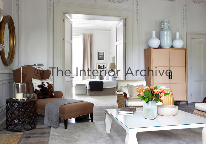 Large double doors lead from the modern and elegant living room to the large master bedroom