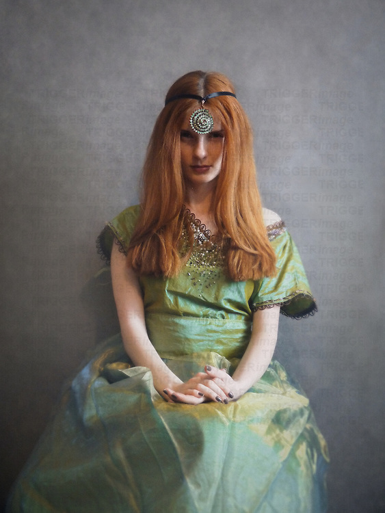 A woman seated, with long red hair, in a vintage green tafeta gown and a large rhinestone headdress on her forehead.