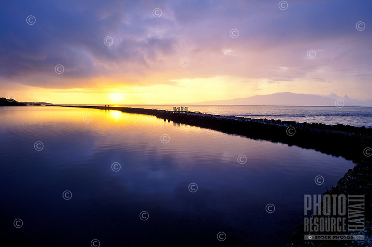 Restored Ualapue Fishpond on the southeastern coast of Molokai at sunrise, with the island of Lanai in the background