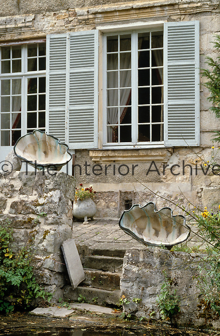 In the garden a pair of giant clam shells tops the wall flanking some stone steps leading to the pond below