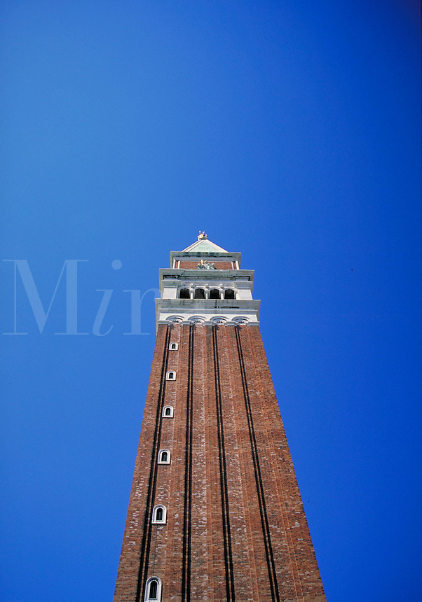 Breathtaking architecture of Venice, Italy. architecture, old brick tower with arched windows on the right hand side only, taken from below, looking up at building against a brilliant, azure blue sky. Venice, Italy.
