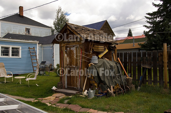 Weathered wooden outhouse behind a house in the town of Leadville, Colorado