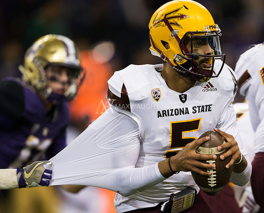 Arizona State quarterback Manny Wilkins evades the grasp of a Husky defender.