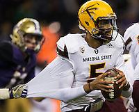Arizona State quarterback Manny Wilkins evades the grasp of a Husky defender.