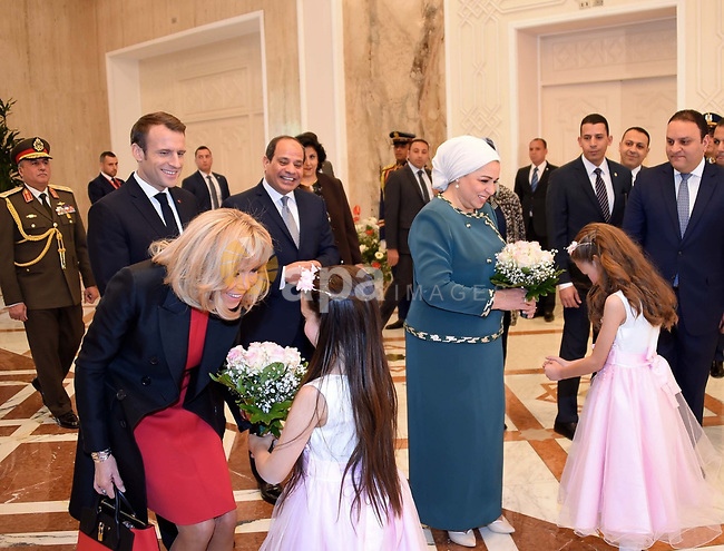 Egyptian First Lady Intissar Amer (R) and Brigitte Macron (L), wife of French President, receiving flowers upon their arrival at the presidential palace in Cairo on January 28, 2019. Photo by Egyptian President Office