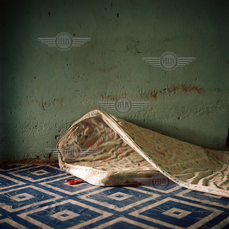 A mattress on the floor of Hannatu's shop. At the end of 2014 she fled Borno with her children when insurgents attacked her village. The militants went from door to door, picking up young boys and girls. Many others were killed. <br /> Hannutu: 'I am a widow since 2009. Since my husband died I take care of the family income. I had a small restaurant in Maiduguri. I had only one goal when my village was under attack, to keep the children safe. I literally threw them out of the window and we ran. We kept running until we were out of reach of the insurgents. I carried the youngest the entire time. It is a miracle we all survived. My landlord provided a portion of her land and the means to start this shop. She supported me until I could take care of myself. I can be independent again and that is the greatest gift anyone could give me.' <br /> Landlord Miriam (left): 'Hannatu is a fighter. She wanted to take care of her family on her own. I only helped her to open this shop. Mothers help each other. I go to her shop as often as I can and I encourage other people in the community to do the same. I also provided land for the borehole. I wasn't doing anything with the land and now it benefits everybody.'