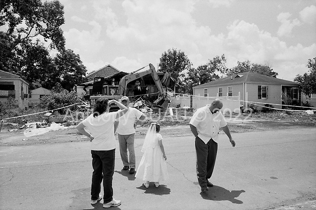 Saint Bernard's Parish, Louisiana.May 27, 2006..Linda and Tony Manalla, who are in their 60s, came to watch their home of 35 years be torn down after it was moved off its foundation by hurricane Katrina. They raised 3 girls in their house and Linda's parents lived just across the street until they died last year a few months before Katrina hit...They have since purchased a home in Slidell. They are joined by their neighbors Reagan Cavignal 7 years old (in white dress), who just made her first communion, and her father as the workers break for lunch...FEMA funded demolition teams work at leveling thousands of  homes in St. Bernard's Parish damaged by hurricane Katrina in August of 2005...FEMA is offering to destroy homes for free up until June 30, 2006. About 12 homes are being demolished daily.