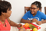 10 year old girl at home in kitchen with mother, talking as mother cuts vegetables for meal