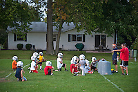 Coaches instruct a youth football practicing on an elementary school field near houses.