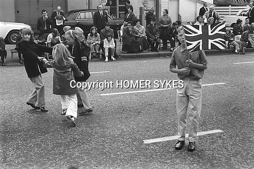 Belfast Orange Day Parade. Protestant children waiting for the parade to come through their neighbourhood. Girls playing Ringa Ringa Rosie, and teen boy with Union Jack flags.