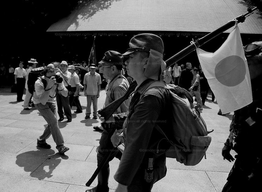Men in imperial army uniforms, one carrying a replica rifle with a Japanese flag tied to it, march through the grounds of the  controversial Yasukuni Shrine during the celebrations of the end of the Pacific War. This shrine houses the spirits of Japan's war dead, including 14 Class A war criminals, and is the centre of focus for Japanase nationalists and source of tension for Japanese neighbors, especially China and Korea who suffered badly at the hands of the Japanese Imperial forces before and during World War 2. Yasukuni Jinja Tokyo, Japan August 15th 2008