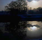 Winter scene of bare trees and clouds reflected in the river Swale. North Yorkshire, England.