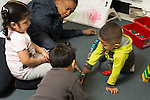 Education preschool female teacher interacting with small group of two boys and a girl playing game with train set