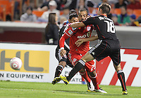 Andy Najar #14 and Devon McTavish #18 of D.C. United hold up Malcon Santos #29 of Toronto FC during an MLS match that was the final appearance of D.C. United's Jaime Moreno at RFK Stadium, in Washington D.C. on October 23, 2010. Toronto won 3-2.