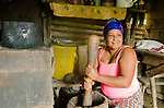 Nancy squats to grind coffee beans for us in a gourd set near her kitchen stove.