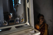 23 year old Priyanka Jena (left) is reflected on the mirror while her mother, Asha Jena speaks to her in their house in Sangam Vihar in New Delhi, India. Photo: Sanjit Das for The Foreign Policy