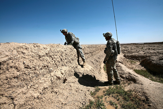 Spc. Tad Collins, 22, of Greensboro, N.C., and Spc. Craig Johnson, 26, of Charleston, S.C., two soldiers with Company A, 2nd Battalion, 2nd Infantry Regiment, cross a mud wall while on patrol in the village of Mir Hotak in Kandahar province, Afghanistan. April 15, 2009. DREW BROWN/STARS AND STRIPES