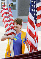 NWA Democrat-Gazette/DAVID GOTTSCHALK  Mary Tomlinson, a member of the Fayetteville Lions Club, carries Monday, September 7, 2015 a handful of United States Flags before installing them on posts on Dickson Street in Fayetteville. The installation of the flags is a service project for the club and are posted through out the city including Dickson Street, the downtown square and parts of College Avenue.