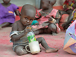 A child with a bottle of milk in a supplemental feeding program for malnourished children and mothers run by the clinic of the Loreto School in Rumbek, South Sudan. The school is run by the Institute for the Blessed Virgin Mary--the Loreto Sisters--of Ireland. Behind them, their mother shells peanuts that are used in the preparation of the food.